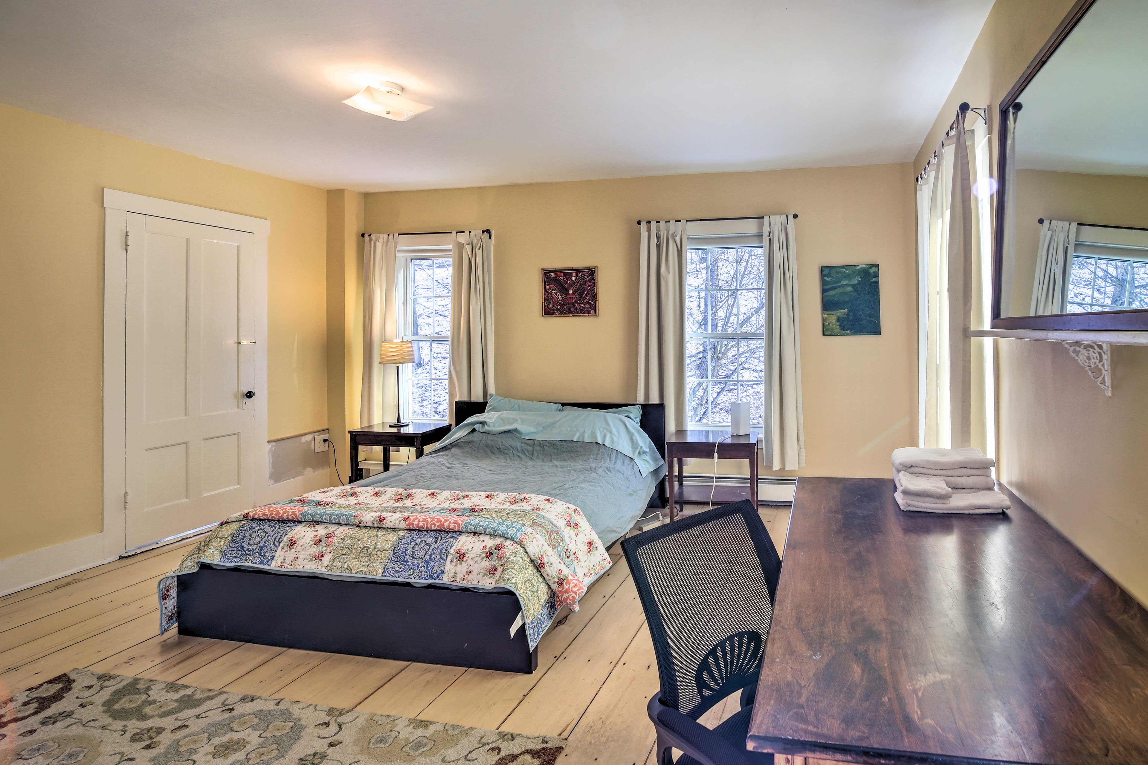 The master bedroom hosts a queen bed and desk.
