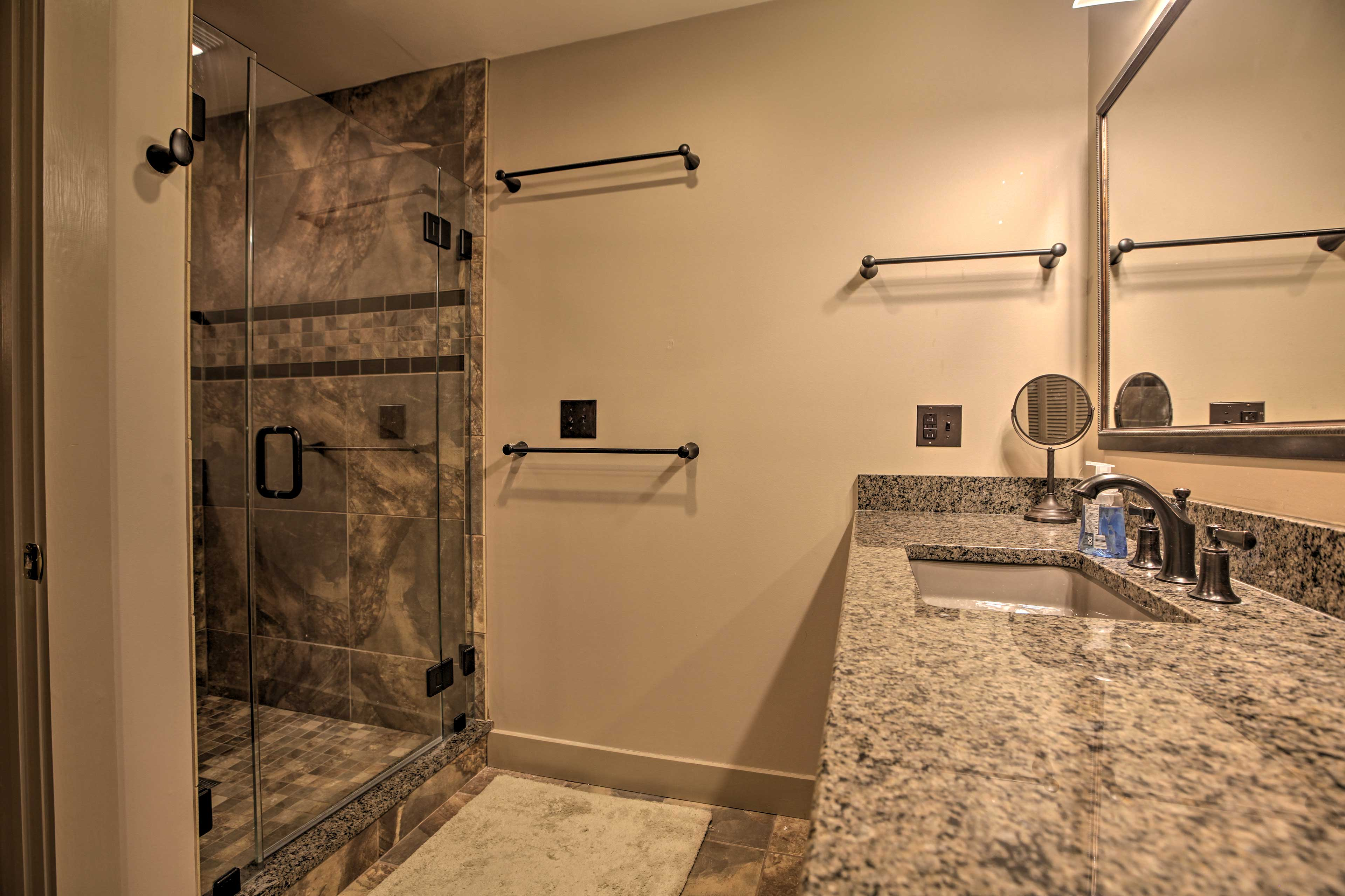 The shower boasts a glass door and designer tile walls.