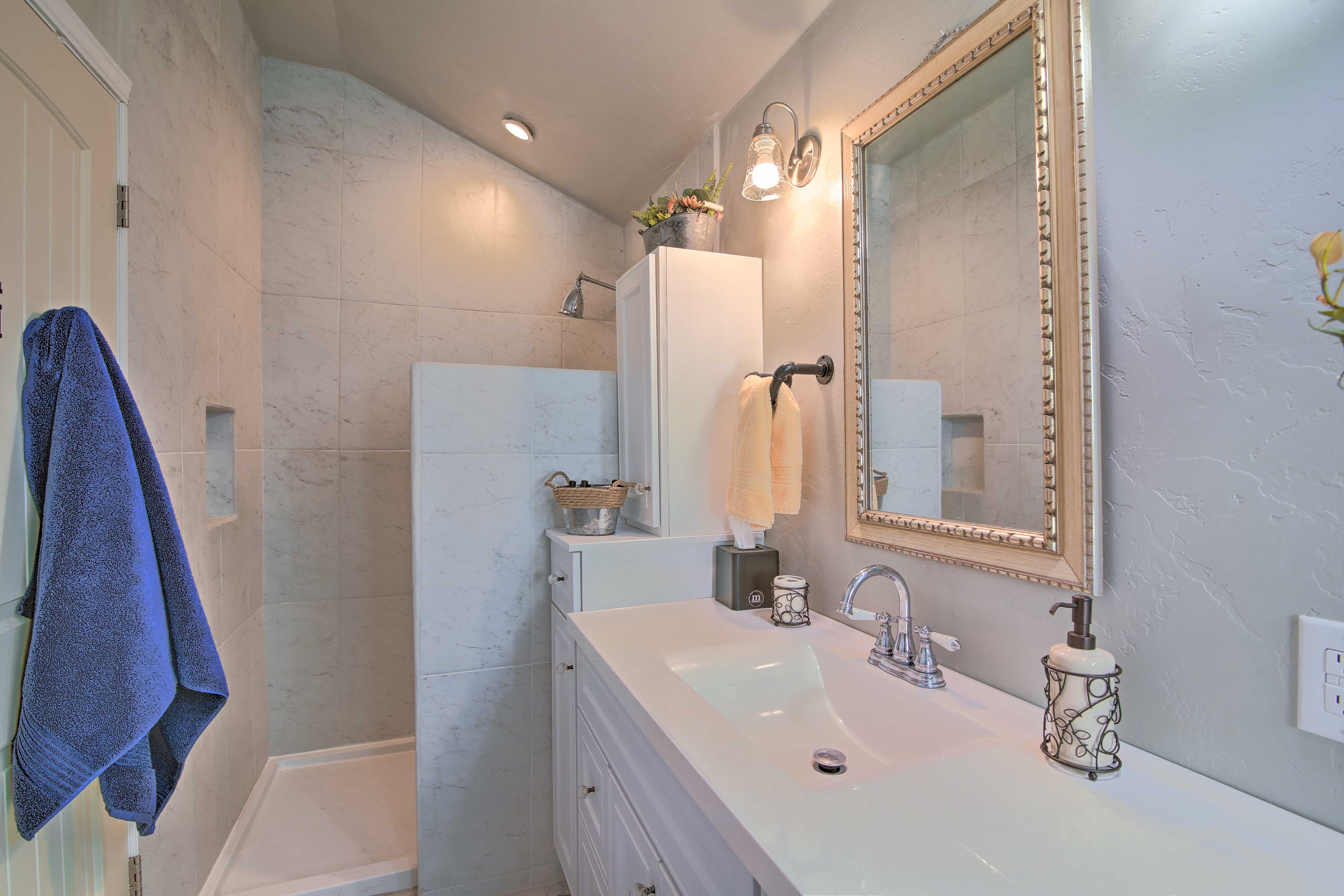 Step into the walk-in shower with stylish, white-granite tiling!