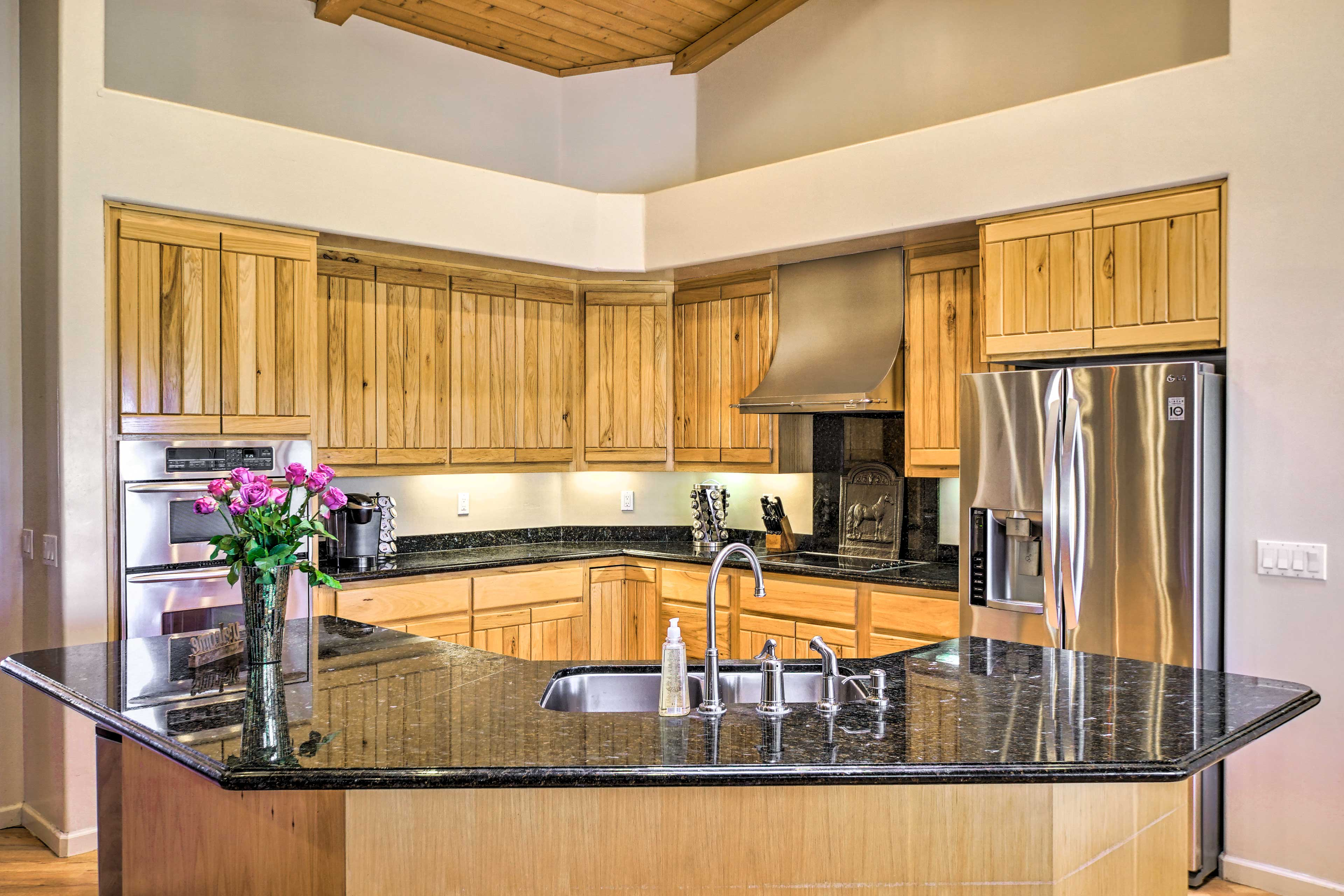 The kitchen features stainless steel appliances and granite counters.