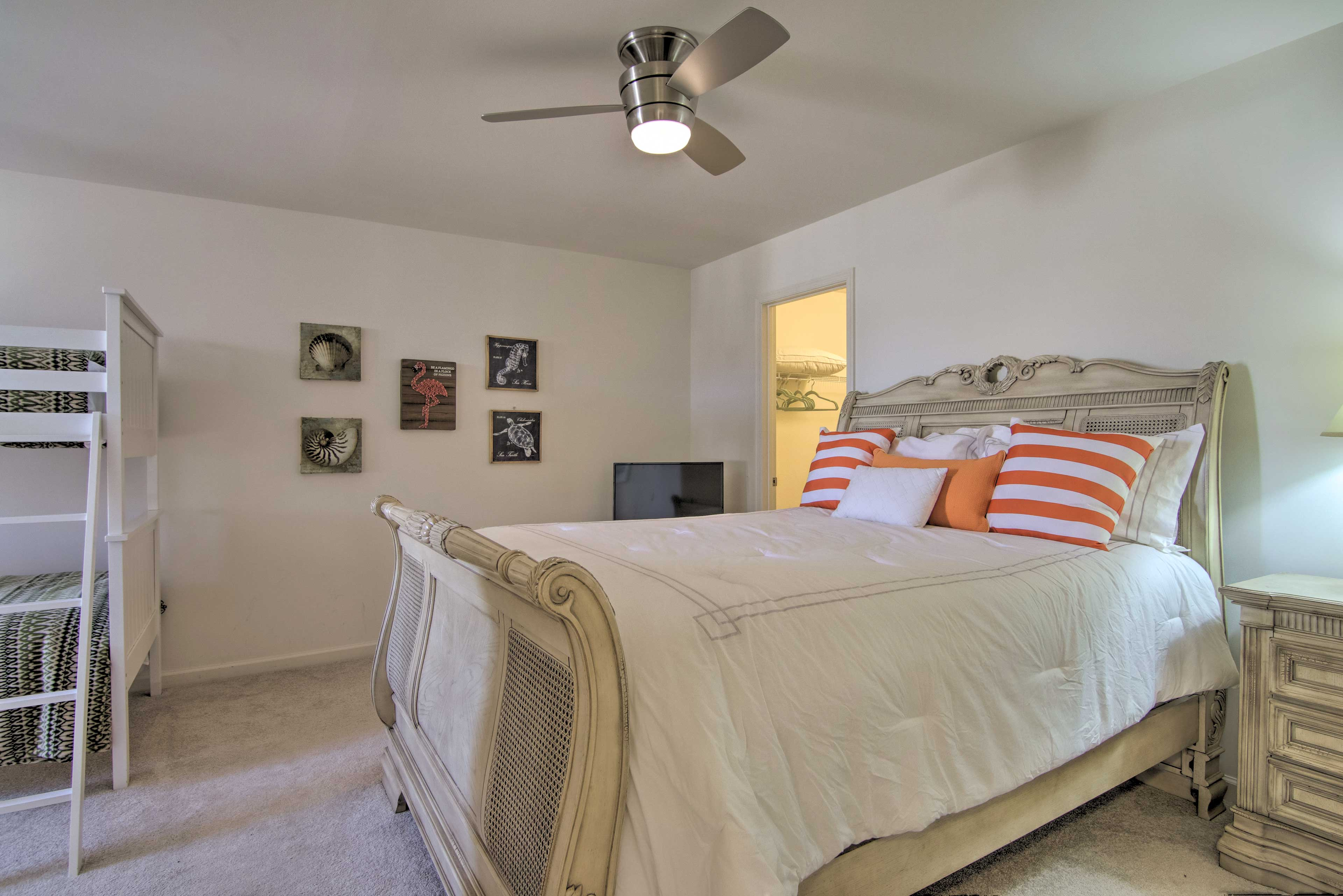 This bedroom features a queen bed as well as a twin bunk bed.