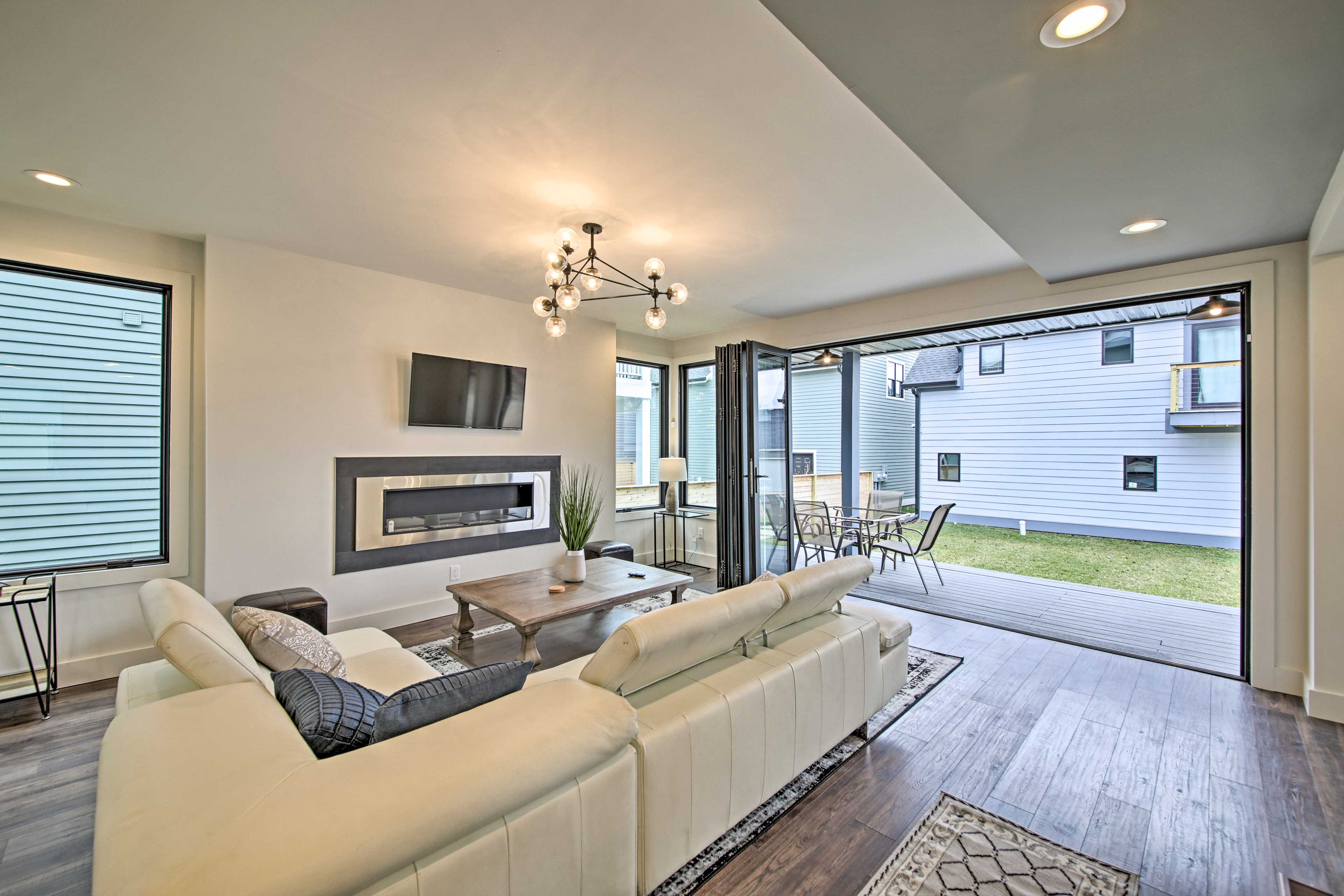 The spacious living room boasts an accordion glass door and modern fireplace.