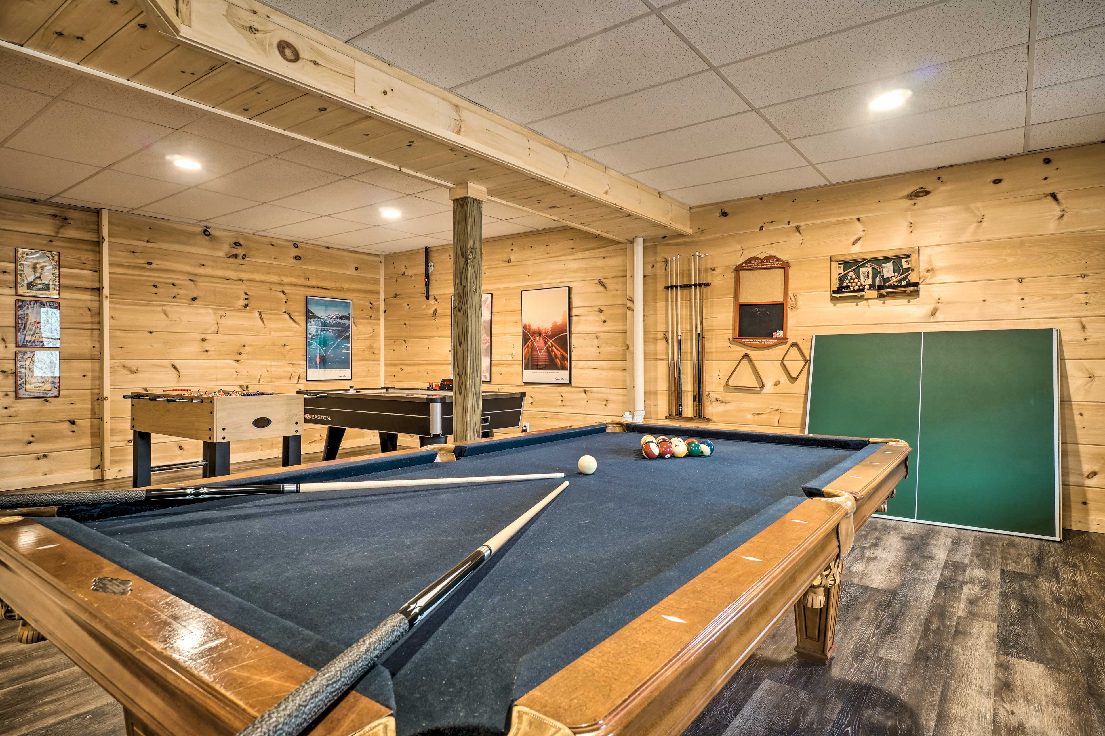 The downstairs game room boasts a pool table, ping pong table, and darts.