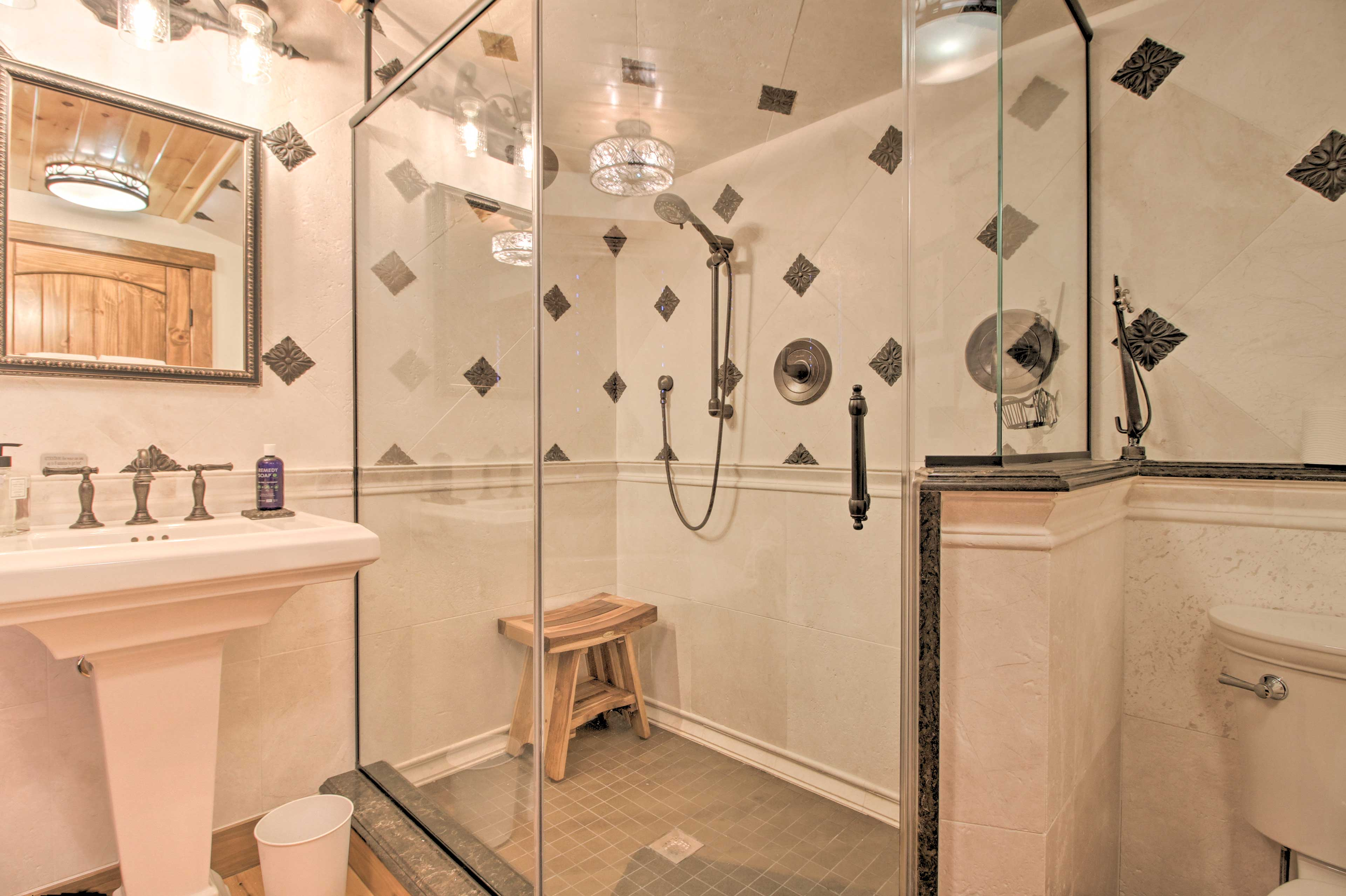Step into the glass-frame shower to rinse off with the detachable shower head.
