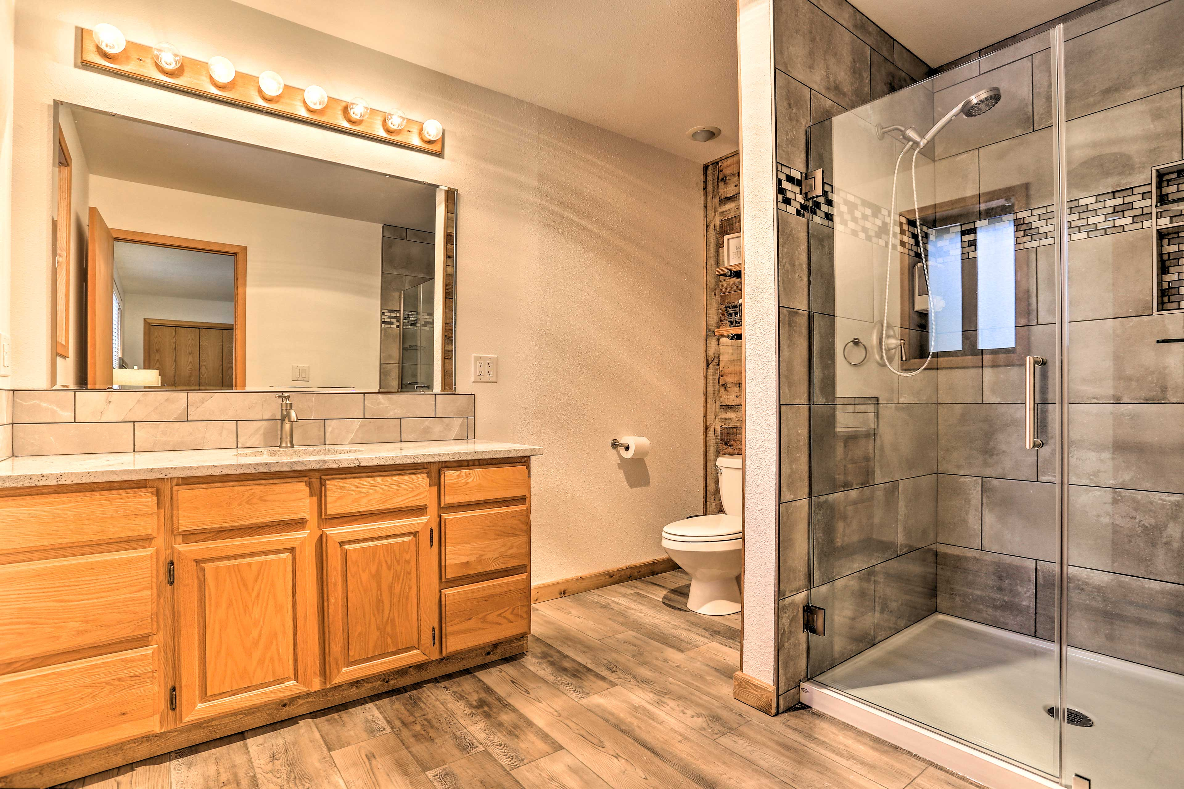 The master bathroom has a glass-frame shower with a detachable shower head.