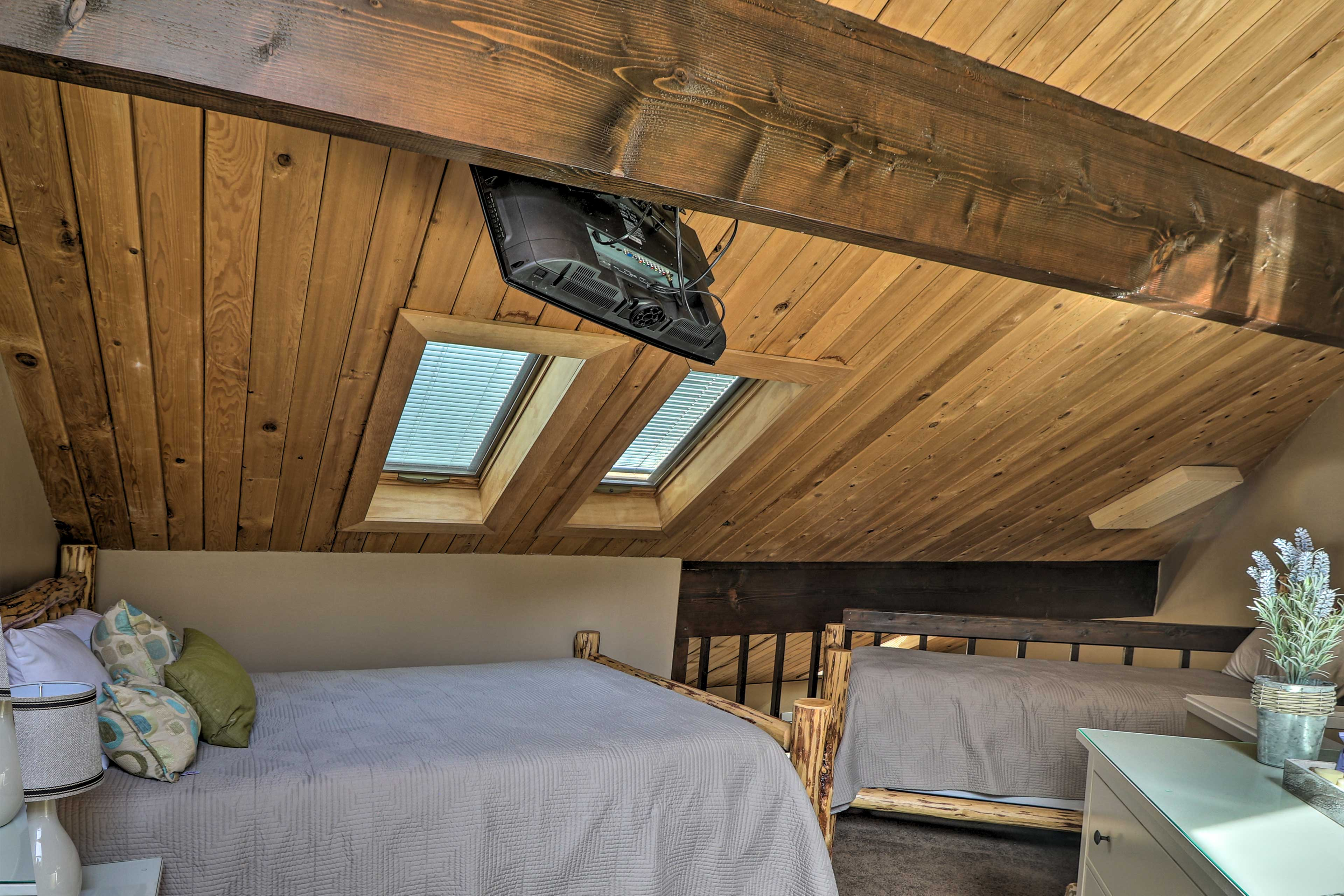 The lofted bedroom features a queen and twin beds.
