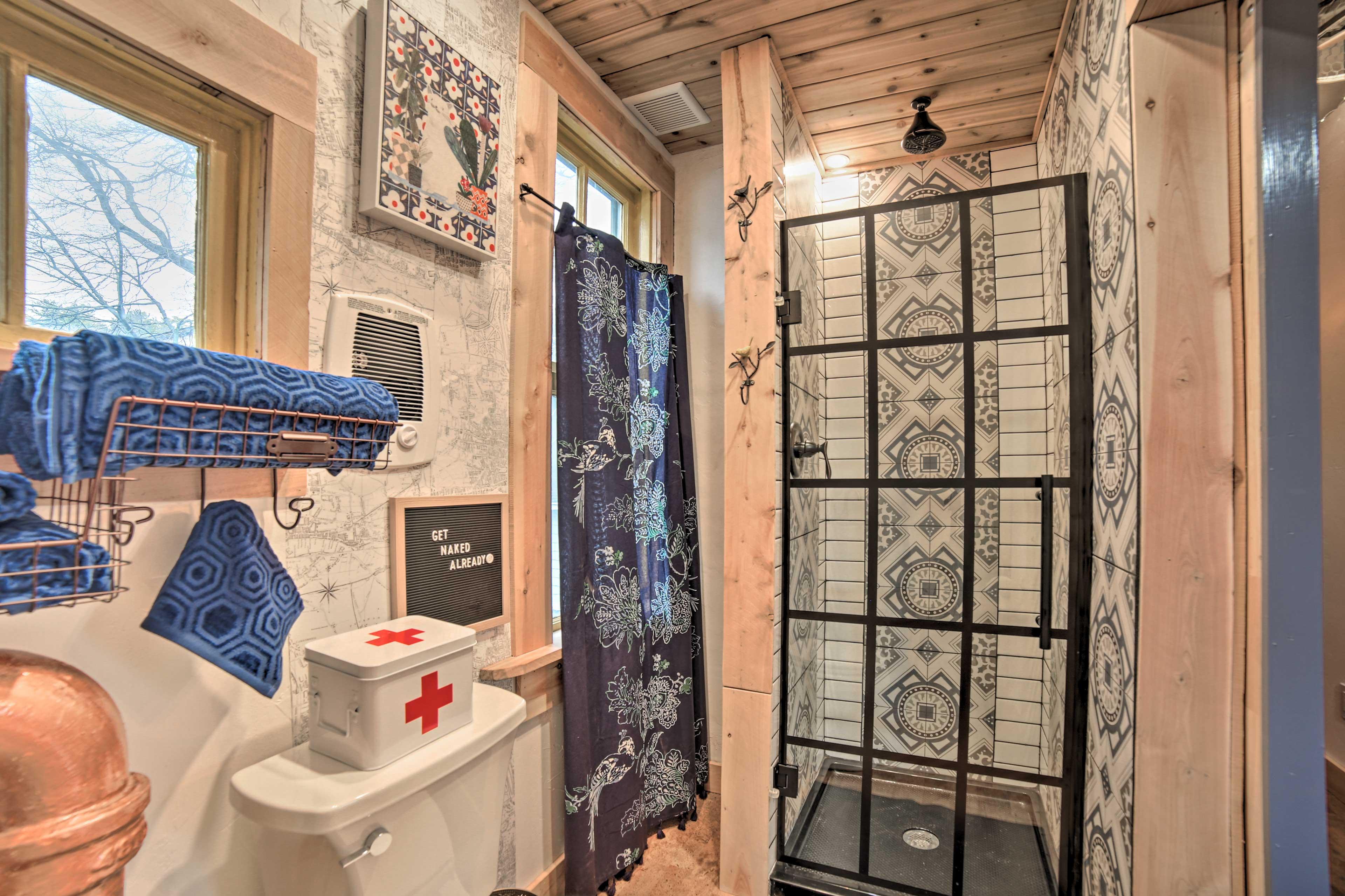 This one-of-a-kind bathroom offers a barrel sink & rain head walk-in shower.
