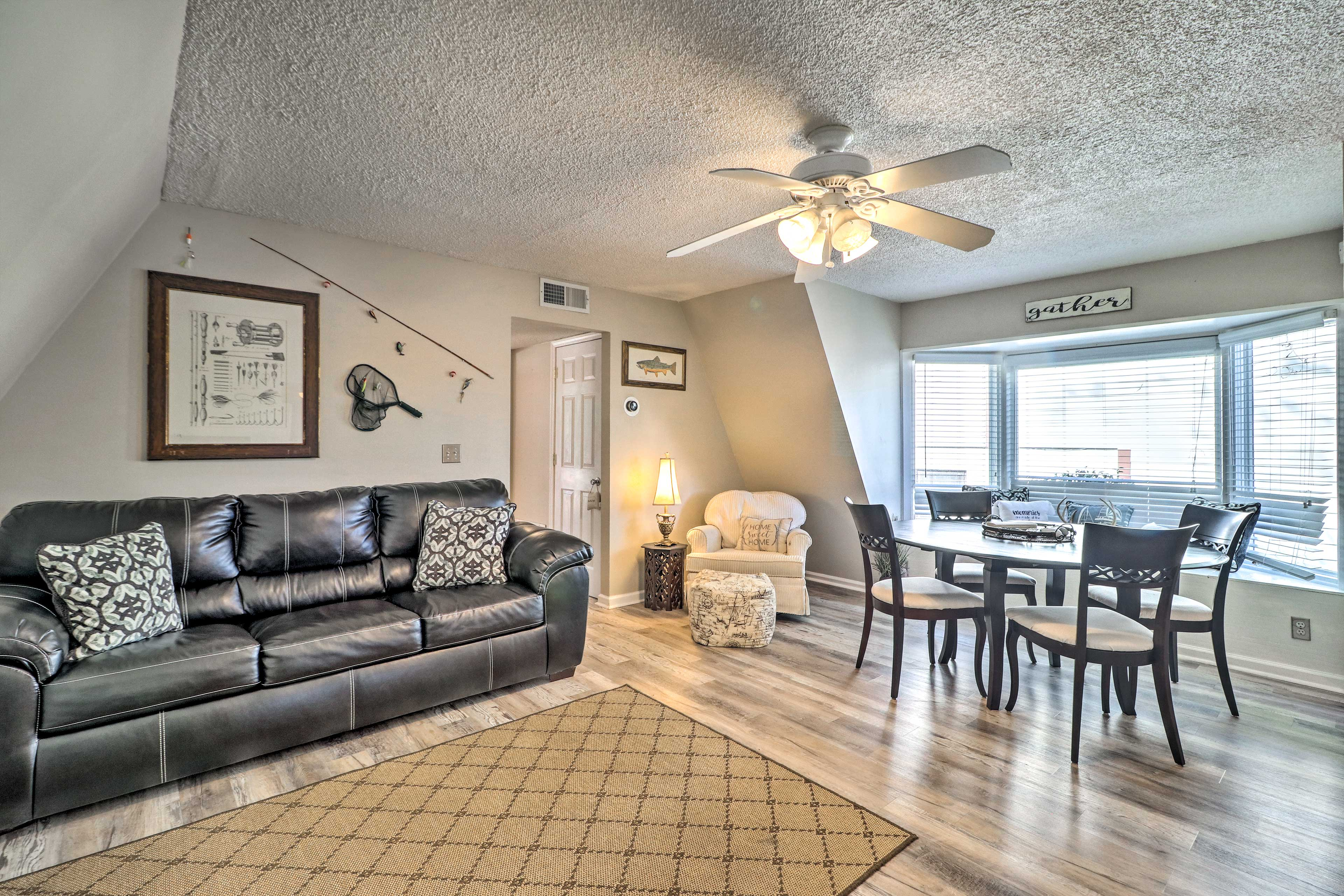 The living room is complete with a leather sofa and dining table.