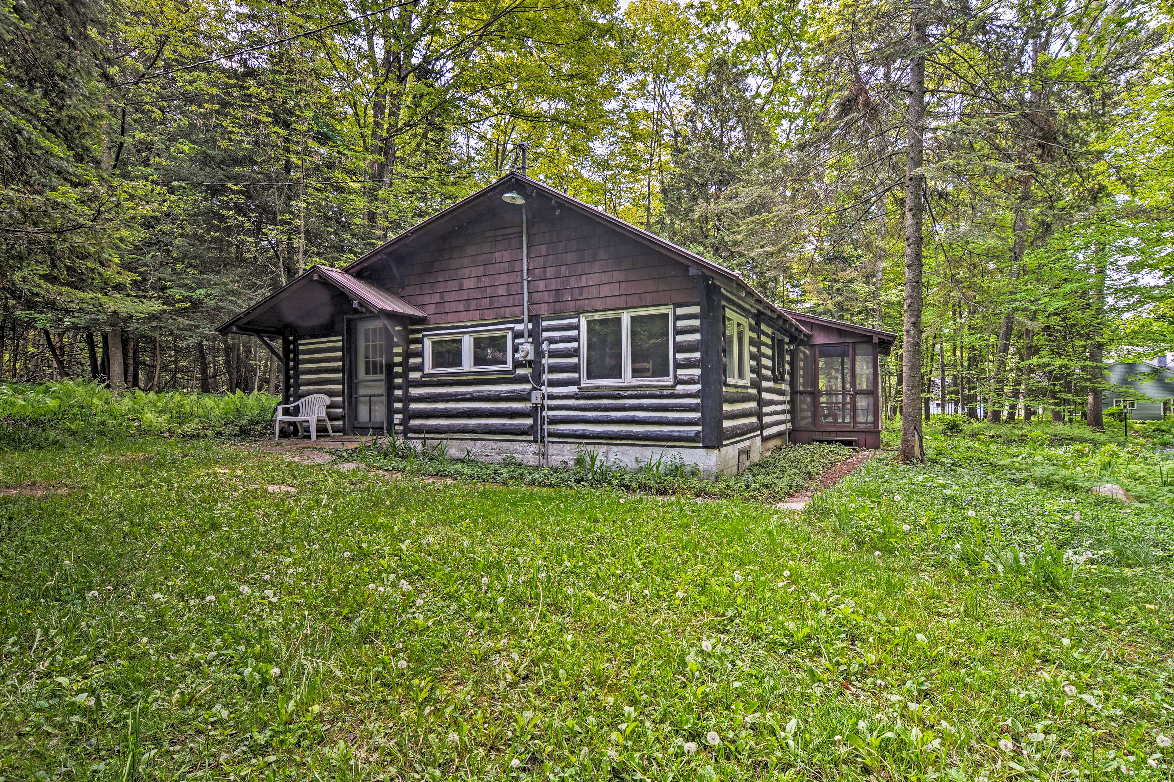 This rustic cabin is nestled in a wooded setting.