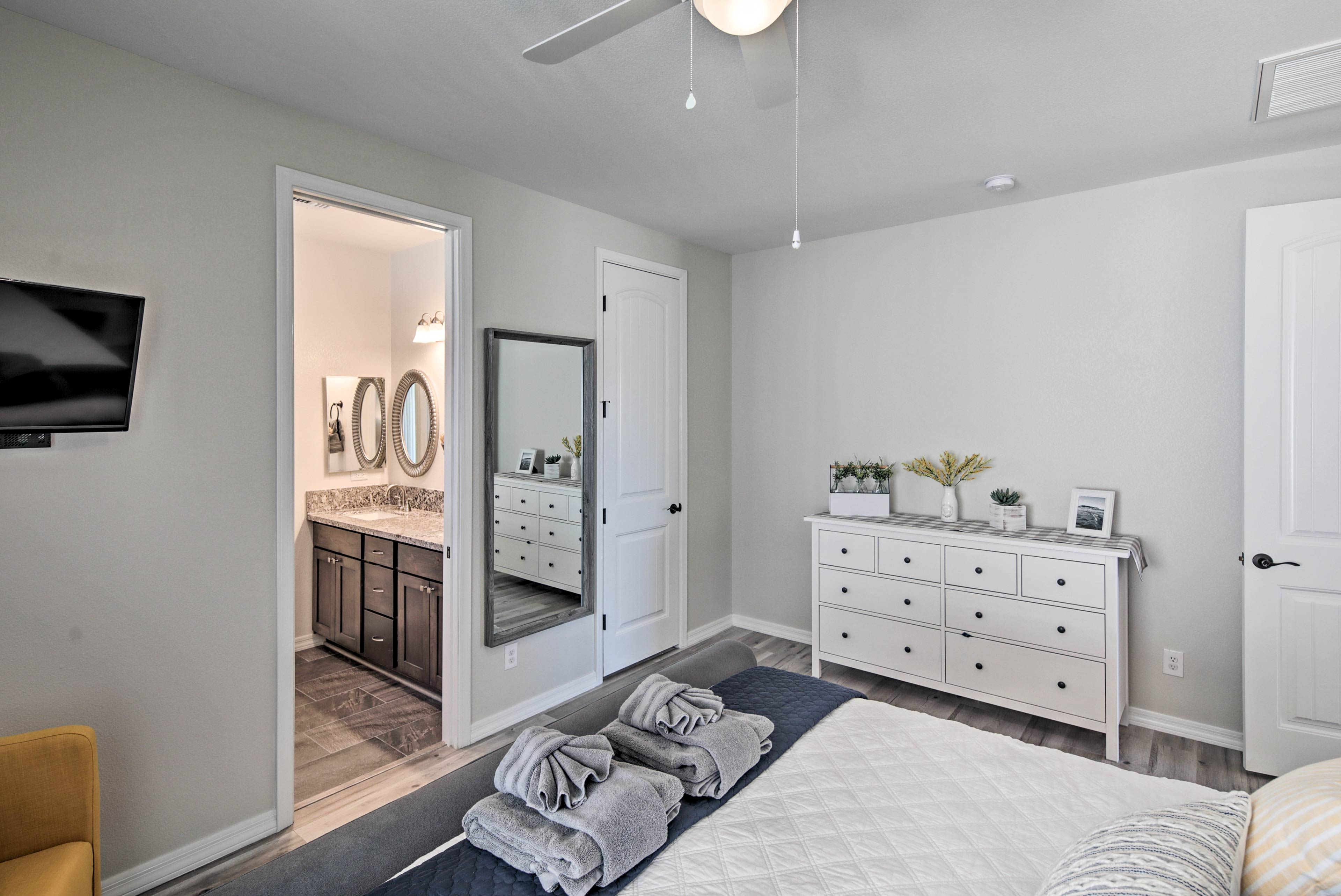 This room has tasteful decor with a white dresser for storage.