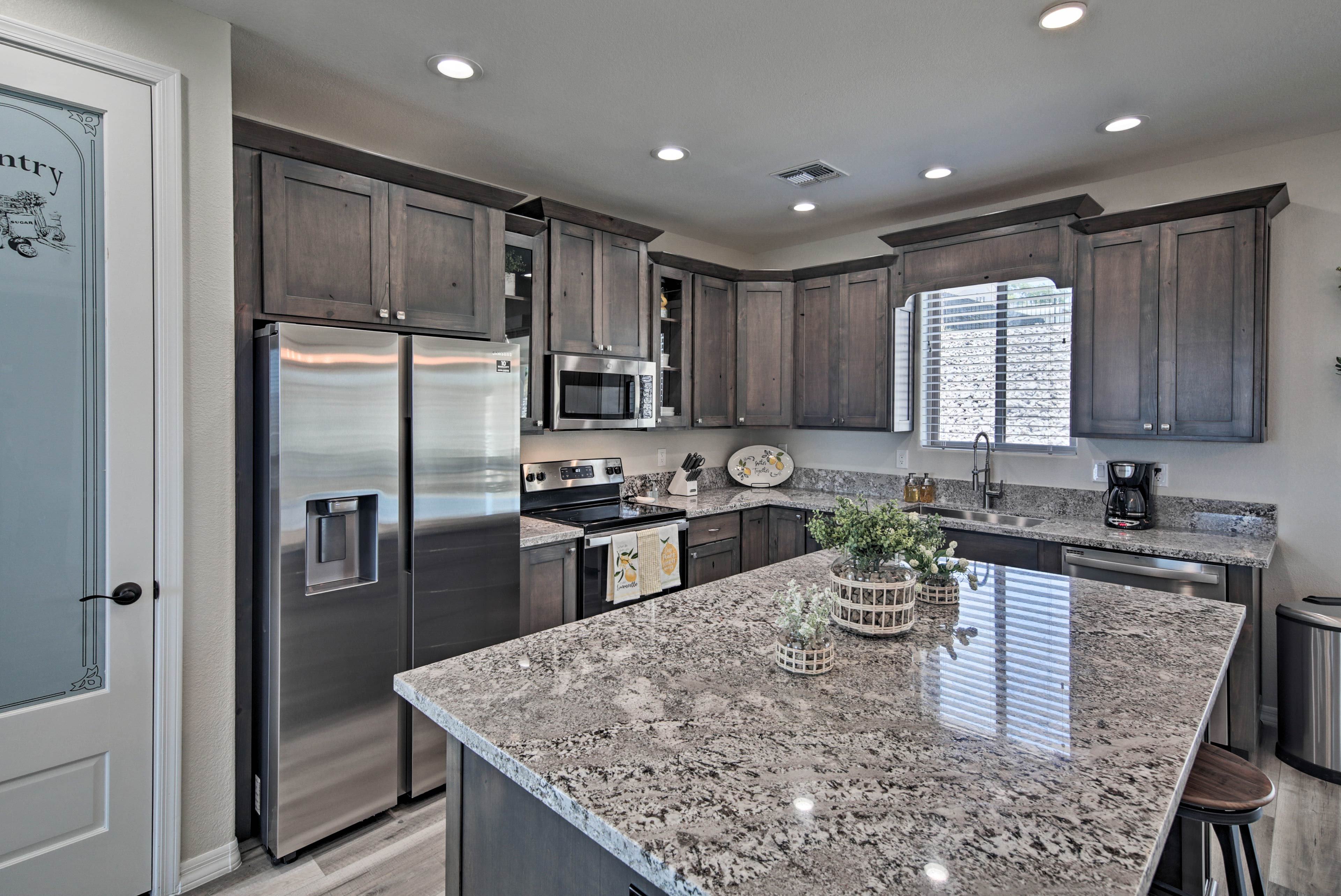 This modern kitchen has stainless steel appliances and granite countertops.