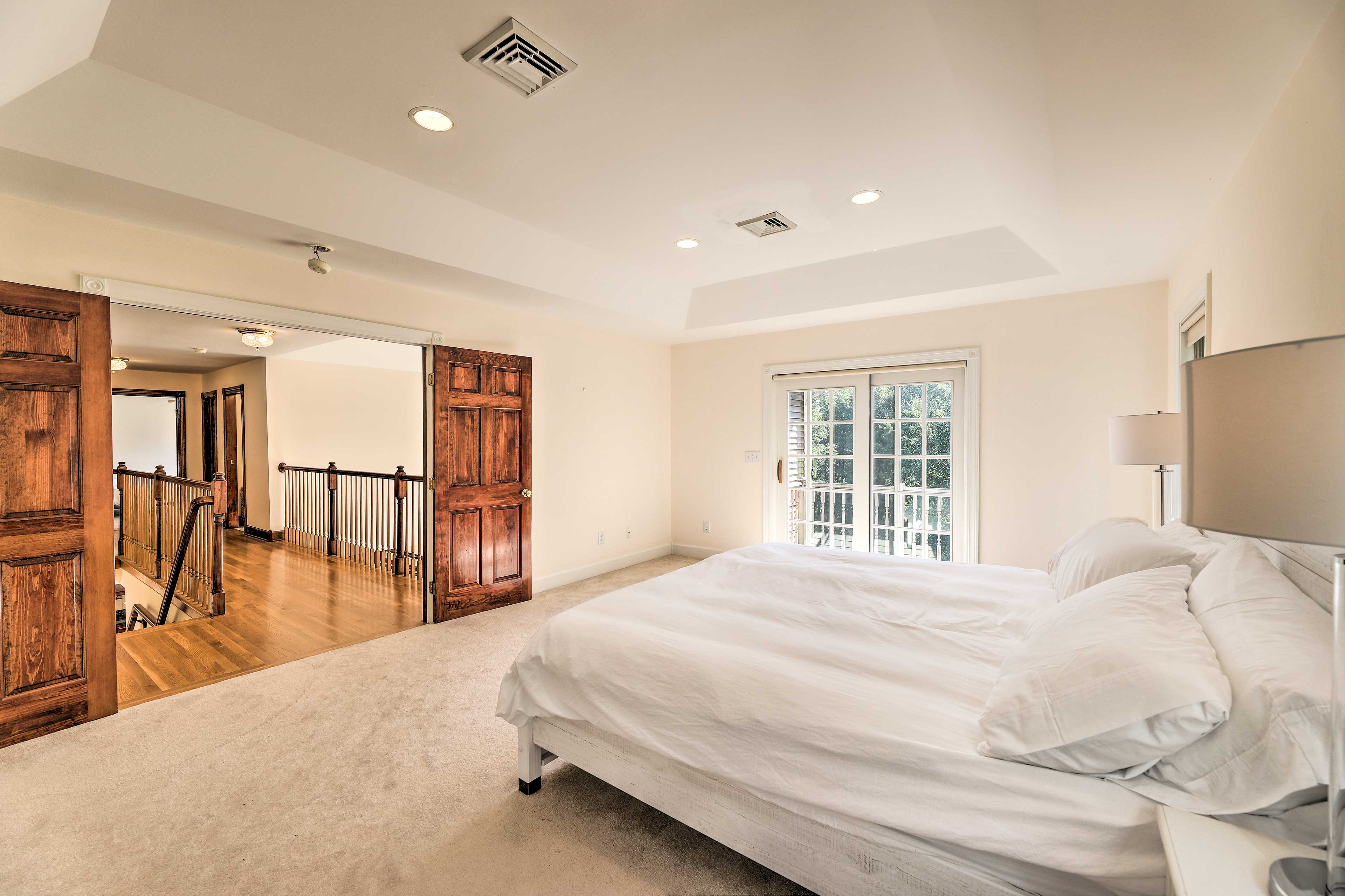 The master bedroom boasts dual doors & a king bed.