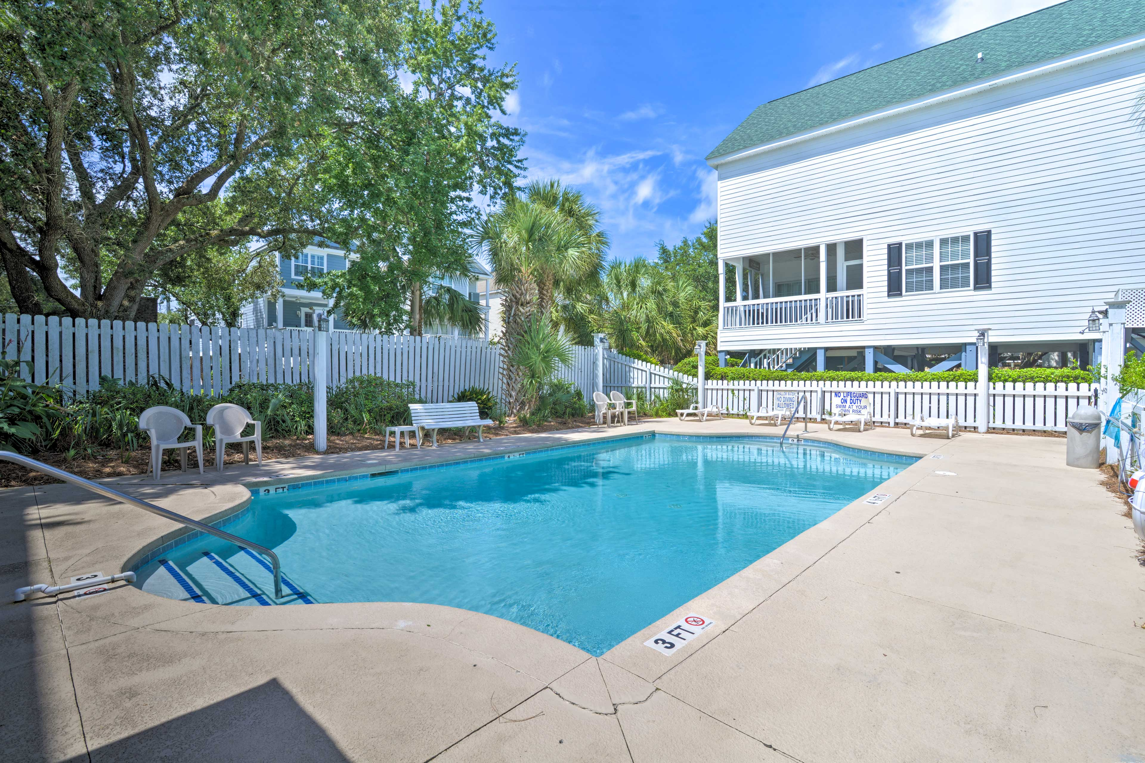 Lounge the day away by the community pool, just steps from this vacation rental.