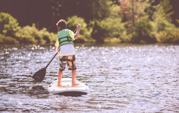 Young child paddleboarding on Table Rock Lake in Branson, MO