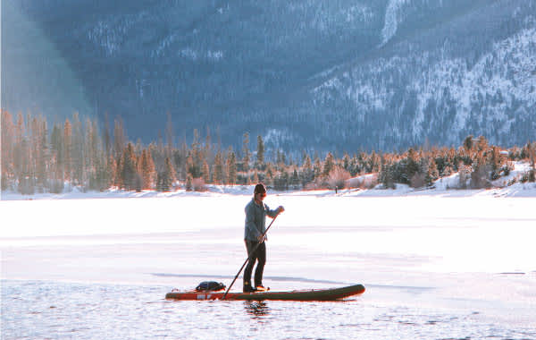 Paddleboarder on snowy Lake Dillon in Summit County
