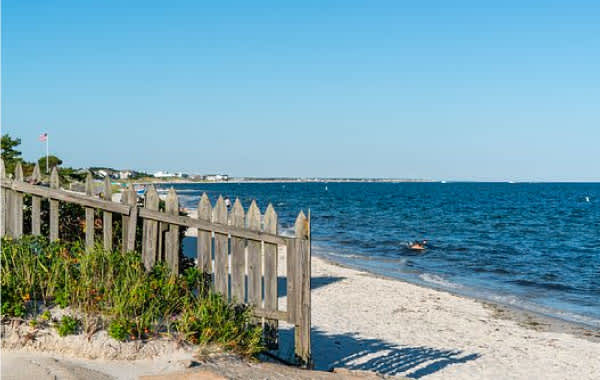 Shoreline in Cape Cod with brown fence and white sand
