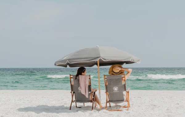 Women beneath umbrella on a white-sand beach in Hilton Head, SC