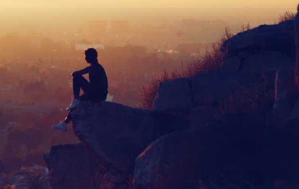Hiker sitting on top of rock in Tucson at sunset.