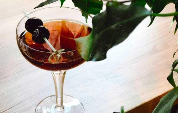 Brown cocktail with cherry garnish