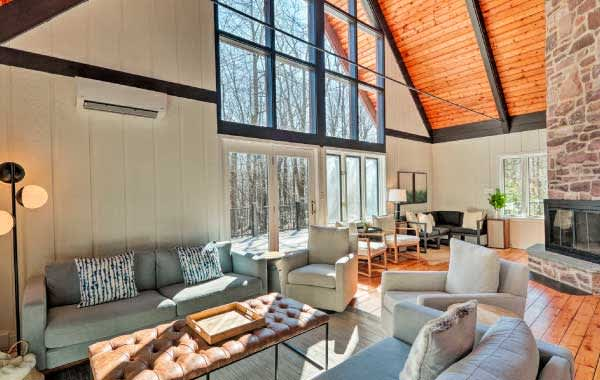 Living room with windows inside of an Evolve vacation rental in the Poconos.