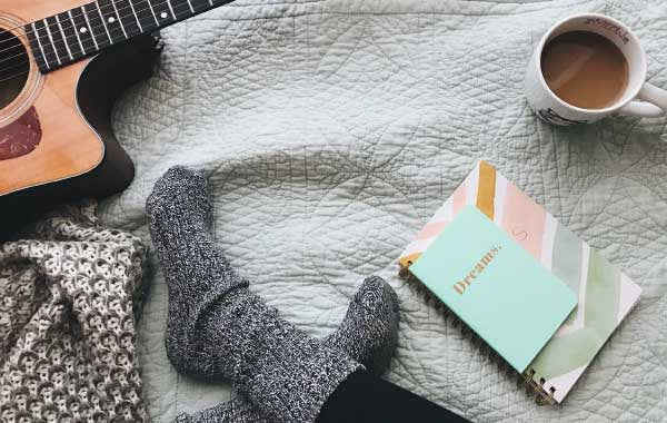 Socks, notebook, coffee cup, and guitar on a white blanket
