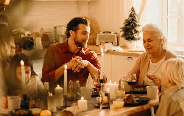 Family gathered at candlelit holiday dinner in a vacation rental