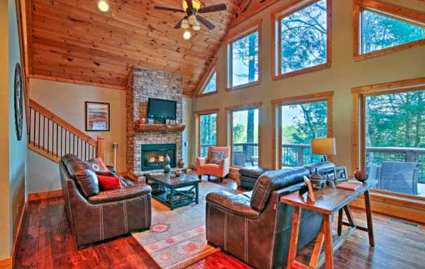 Living room with fireplace, wood floors, and leather chairs inside Evolve vacation home in Blue Ridge