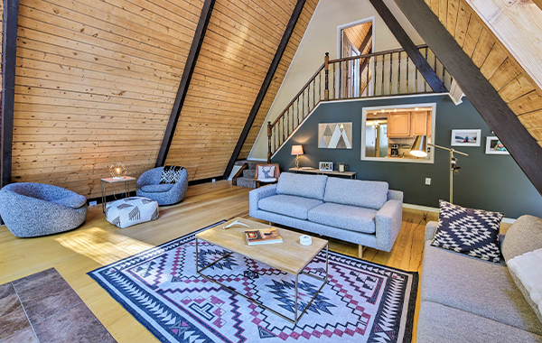Gray couch and wood coffee table inside A-Frame cabin