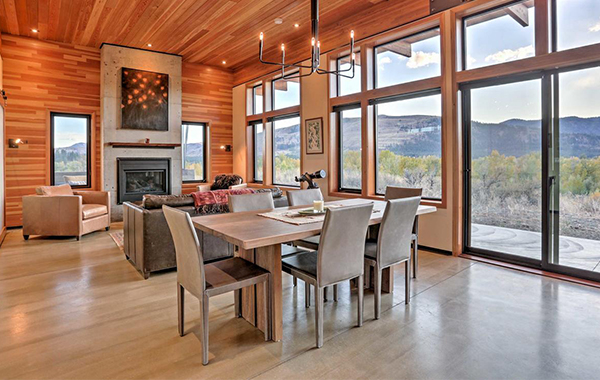 Dining room table, living room furniture, and chandelier in home with wood panels