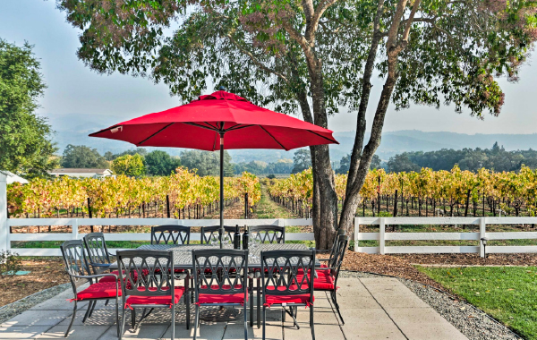 A big glass table sits just feet from a vineyard on the sunny back patio of this Sonoma, California vacation rental.