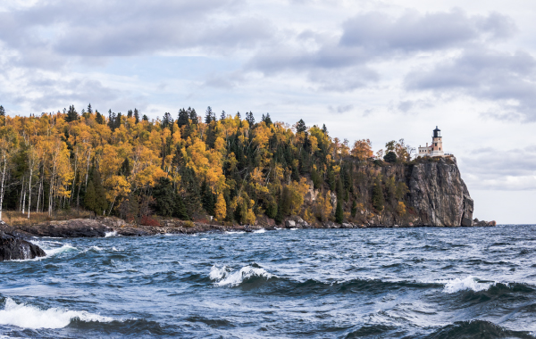 View of Split Rock Lighthouse in Minnesota, surrounded by water and fall foliage