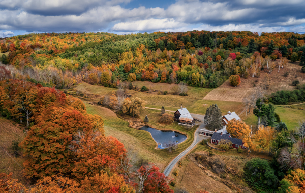 A barn nestled in a valley with sweeping fall foliage views in Vermont
