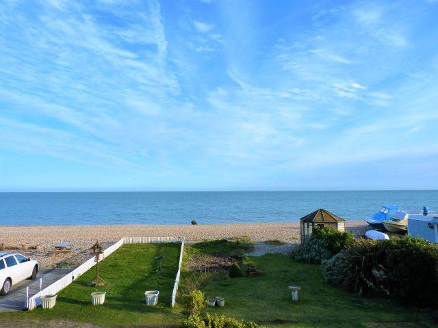 Balcony view over garden, beach and sea