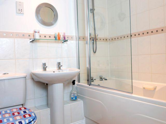 Family bathroom has a bath and shower over