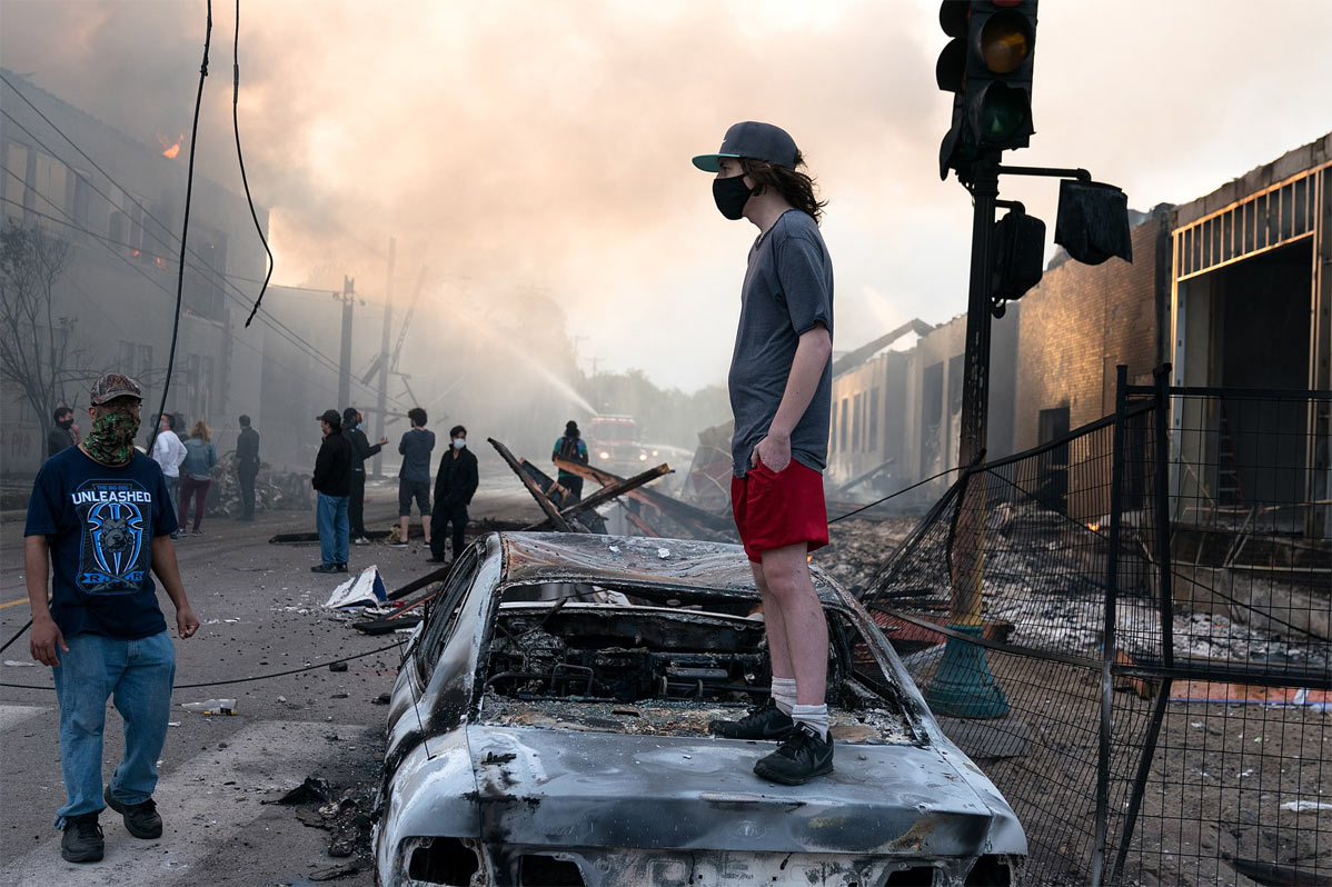 A man stands on a burned out car. Fires seen burning behind him at the Lake St area of Minneapolis, Minnesota.