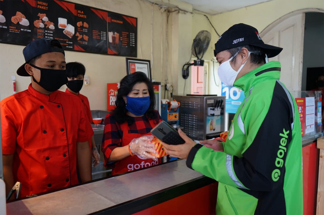 A Gojek driver orders food from a restaurant for his customer amid coronavirus pandemic