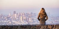 woman sitting on a stone wall looking out at a city