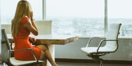A woman in a red business dress talks on a phone while looking over a skyline in an office chair