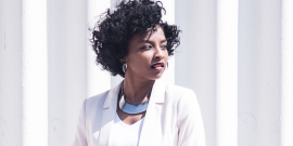 Black woman in a white suit looking off to the side