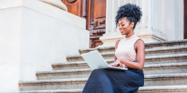 professional woman sitting on steps working on a computer