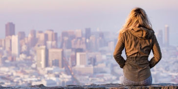 Woman in front of city