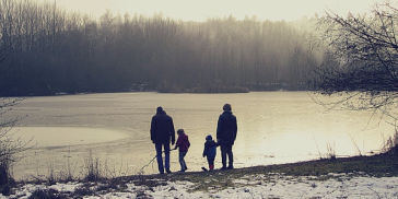 Grandparents and grandchildren by a lake in winter
