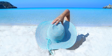 Retired woman wearing a hat on the beach