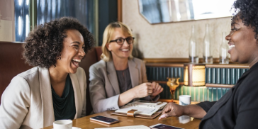 women laughing in a business meeting