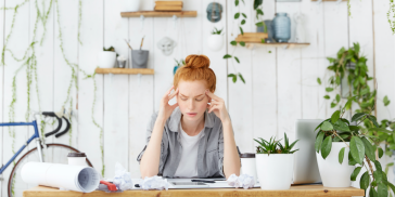 A stressed woman at work, head in her hands