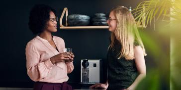 two women talking by a coffee machine