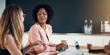 women talking in a boardroom