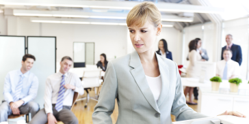 woman looking uncomfortable as male colleagues look on