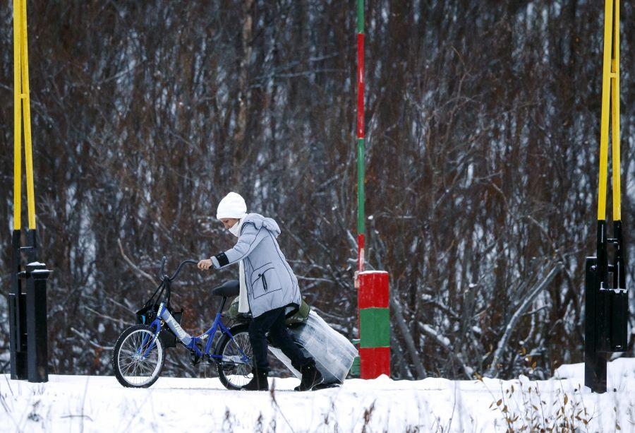 En kvinne med sykkel og koffert passerer den norsk-russiske grensen på Storskog i Finnmark i 2015.