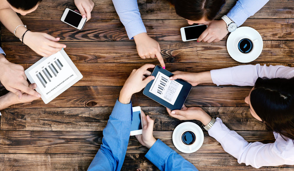 overhead view of a team of people working together with tablets and phones